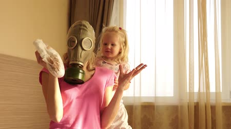 respiração : A woman in a gas mask changes a dirty baby diaper with disgust. Mother and child.