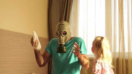 отцовство : A man in a gas mask with disgust changes a dirty baby diaper. Father and child.