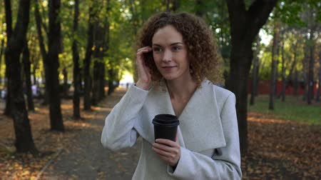 elvihető : Business lady drinking coffee in the autumn Park. Woman in Park. Stock mozgókép