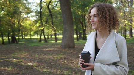 навынос : Autumn, business woman drinks coffee in the autumn park.