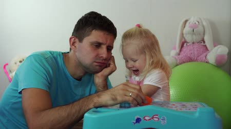 перегружены : A tired father man plays with a child in a room.