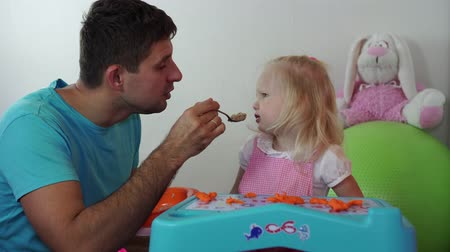níveis : father is trying to feed his daughter. The child does not want to eat porridge.
