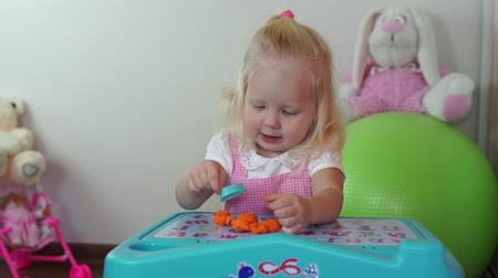 mold : Childrens creativity. Child girl sculpts from plasticine at the table.