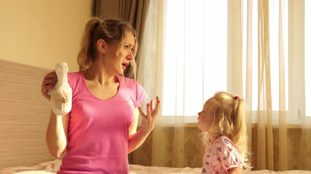 unpleasant smell : A woman holds a dirty diaper with disgust. The child and mother in the room. Stock Footage