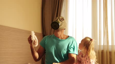 unpleasant smell : A young father in a respirator changes a dirty baby diaper.