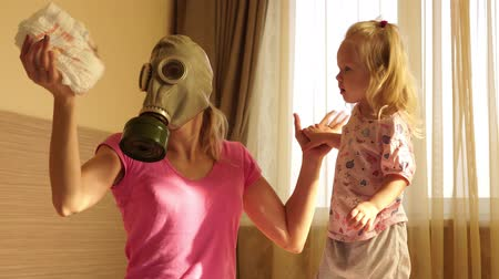 unpleasant smell : A child and a woman in a gas mask change dirty baby diapers.