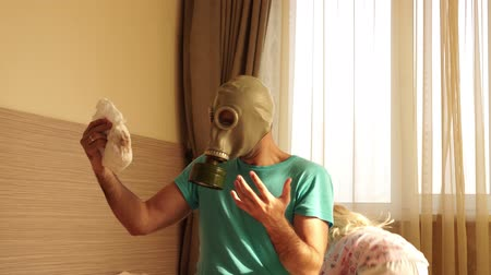 unpleasant smell : A man in a gas mask changes dirty diapers. Young father and child. Stock Footage