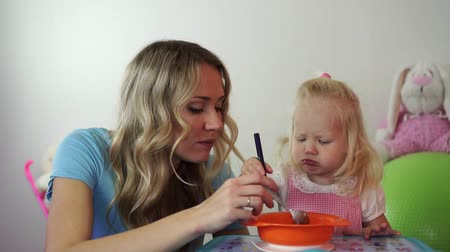 zabkása : Mom feeds baby porridge with a spoon.