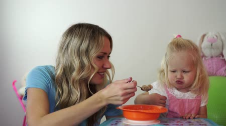 gruel : child is a girl blonde naughty and does not want to eat. Mom feeds the baby with a spoon. Stock Footage