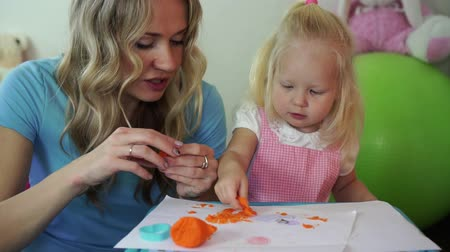 пластилин : Beautiful blondes mom and daughter sculpt from plasticine at the table.