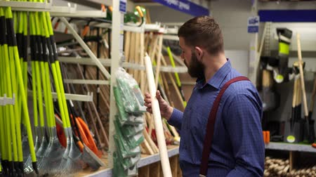 brusič : Male buyer in the hardware store chooses a shovel.