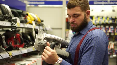 comparar : A man in a hardware store chooses a power tool.