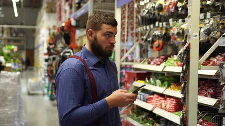 аппаратные средства : A man with a smartphone in a hardware store.