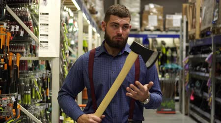 топор : A man with an ax in a hardware store.
