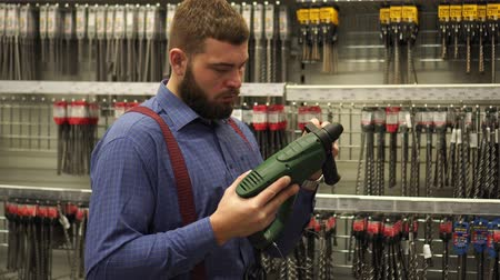 bretels : A man in a hardware store chooses an electric hammer drill.