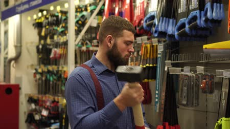 srovnávat : A man in a hardware store chooses a sledgehammer.