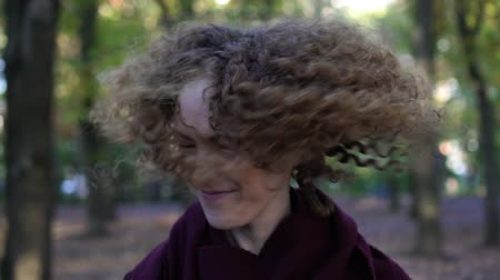 кудри : Portrait of a young beautiful woman with curly hair, slow motion.