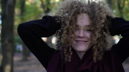 кудри : Young woman shakes curly hair, slow motion.