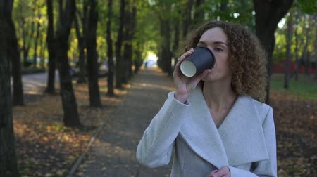 テイクアウェイ : Young business woman is drinking coffee in the autumn park.