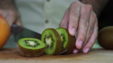 snijplank : A man cuts kiwi, close-up. The man is cutting fruit in the kitchen.
