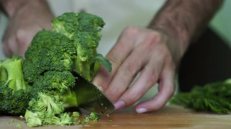 snijplank : A man cuts broccoli in the kitchen. Vegetarian, healthy food.