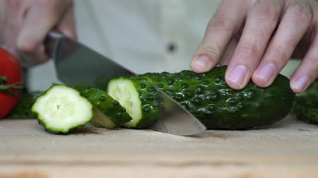 snijplank : A man cuts a cucumber. Man cuts vegetables in the kitchen. Stockvideo