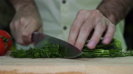 snijplank : A man cuts the dill. Man cuts vegetables in the kitchen. Stockvideo