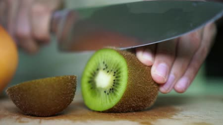 snijplank : Man snijdt kiwi. De man snijdt fruit in de keuken, slow motion. Stockvideo