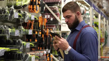 hatchet : A man with a beard chooses an axe in a hardware store.