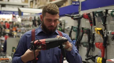 аппаратные средства : A man with a beard chooses a power tool in a hardware store. Стоковые видеозаписи