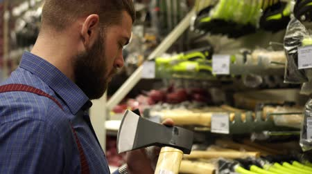 аппаратные средства : A man with a beard buys an axe in a hardware store.