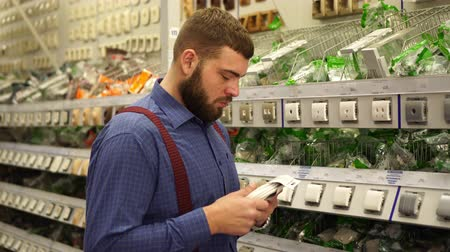 аппаратные средства : A man in a hardware store chooses electrical goods.