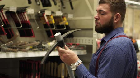 comparar : A man with a beard chooses a hand tool in a hardware store. Stock Footage