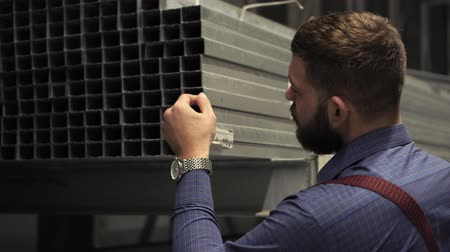 bretels : A man with a beard chooses building materials in a hardware store.