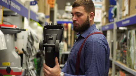 lakásfelújítás : Brutal man with a beard in a hardware store chooses tools. Stock mozgókép