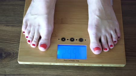 tartmak : Woman weighed on the floor scales.