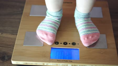 mensen massa : child is weighed on the floor scales