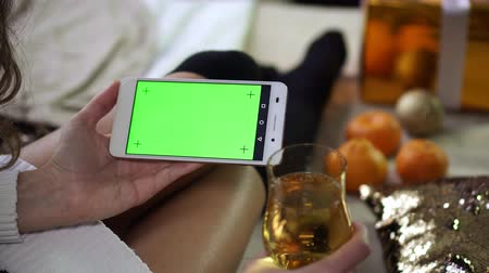 érintőképernyő : Woman holding a glass of champagne and a smartphone with a green screen. Stock mozgókép