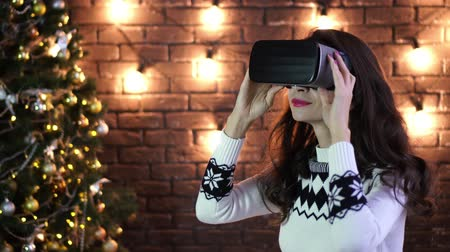 atmosféra : Young woman using Virtual Reality Glasses. VR. Retro loft Christmas background with light bulbs Dostupné videozáznamy