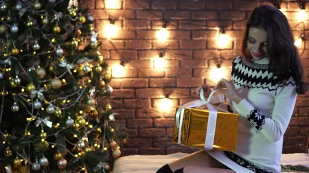 получать : Young woman with gift box on Christmas or new year tree background.