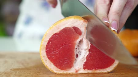grejpfrut : A woman cuts a grapefruit with a knife.
