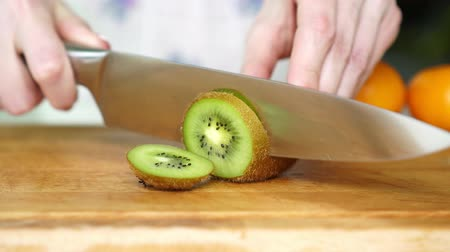 snijplank : A woman cuts a knife kiwi in the kitchen, close-up.