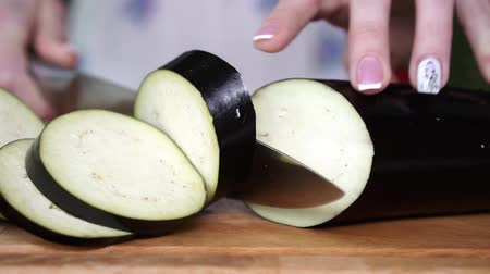 beringela : Woman cutting eggplant in the kitchen, slow motion.