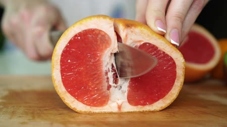 grejpfrut : Woman cutting grapefruit in the kitchen, slow motion.