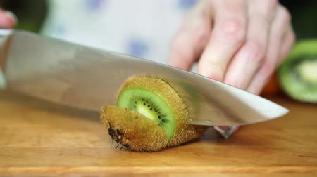 tábua de cortar : Woman cuts kiwis in the kitchen, slow motion.