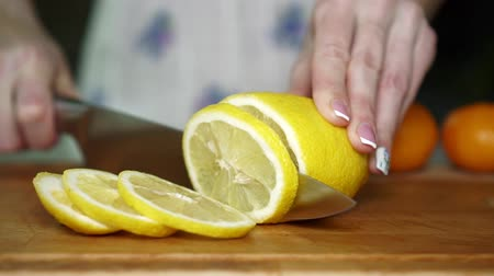 frescura : Woman cutting lemon in the kitchen, slow motion. Vídeos