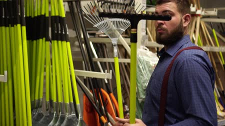 comparar : A man in a hardware store. The buyer chooses a farmer garden tool.