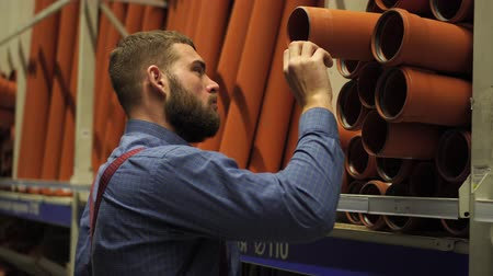 аппаратные средства : A man in a hardware store chooses plastic pipes.