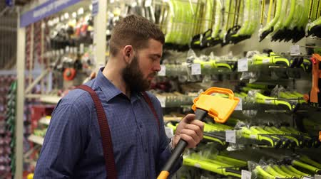comparar : A man in a hardware store chooses an axe.