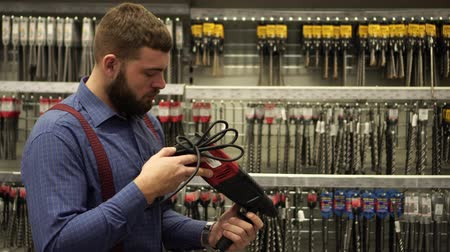 покупатель : A man in a hardware store chooses a drill.